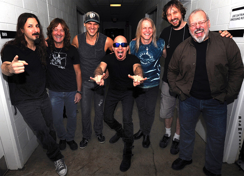 L to R: Bryan Beller, Dave LaRue, Van Romaine, Joe Satriani, Steve Morse, Marco Minnemann, Mike Keneally